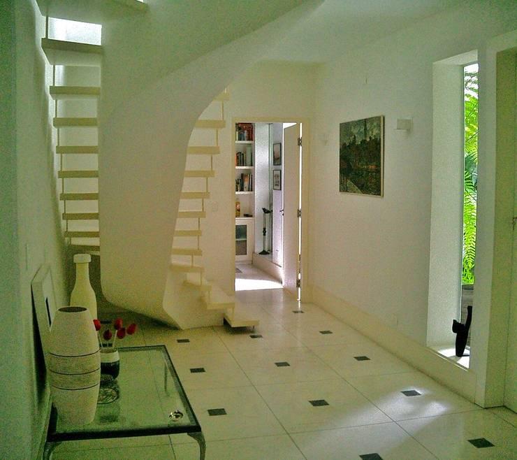 Hall interno com escritório ao fundo: Corredores e halls de entrada  por Kika Prata Arquitetura e Interiores.,