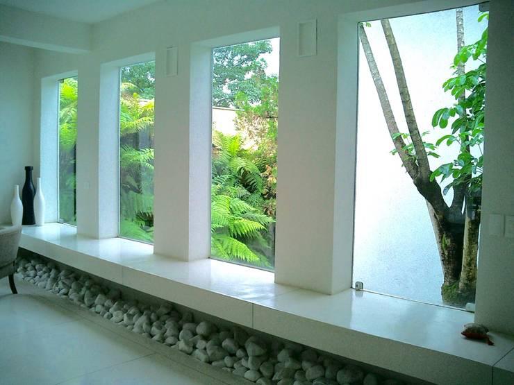 Bancada do ambiente social rodeada por jardim tropical : Janelas   por Kika Prata Arquitetura e Interiores.,