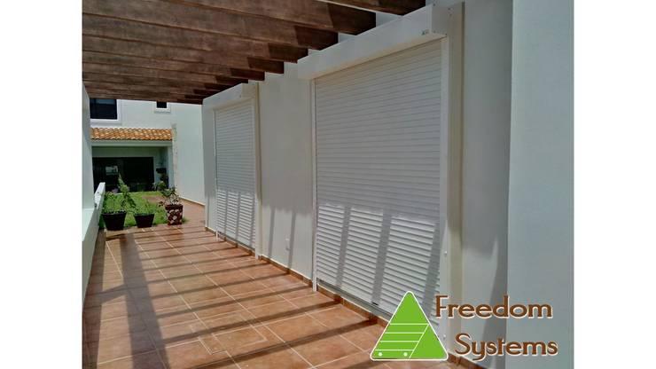 Persianas enrollables de aluminio: Terrazas de estilo  por FREEDOM SYSTEMS MEXICO