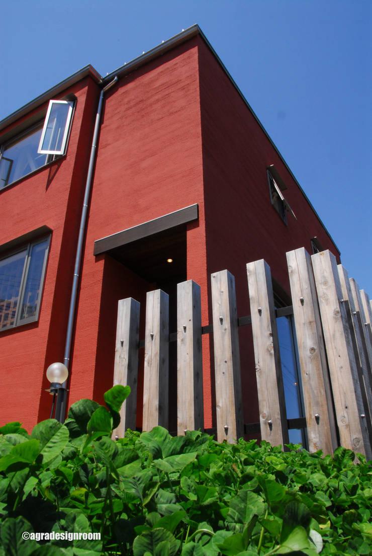 煉瓦色の塗り壁。外の世界と柔らかく繋ぐ105角の木柵。: アグラ設計室一級建築士事務所 agra design roomが手掛けた家です。