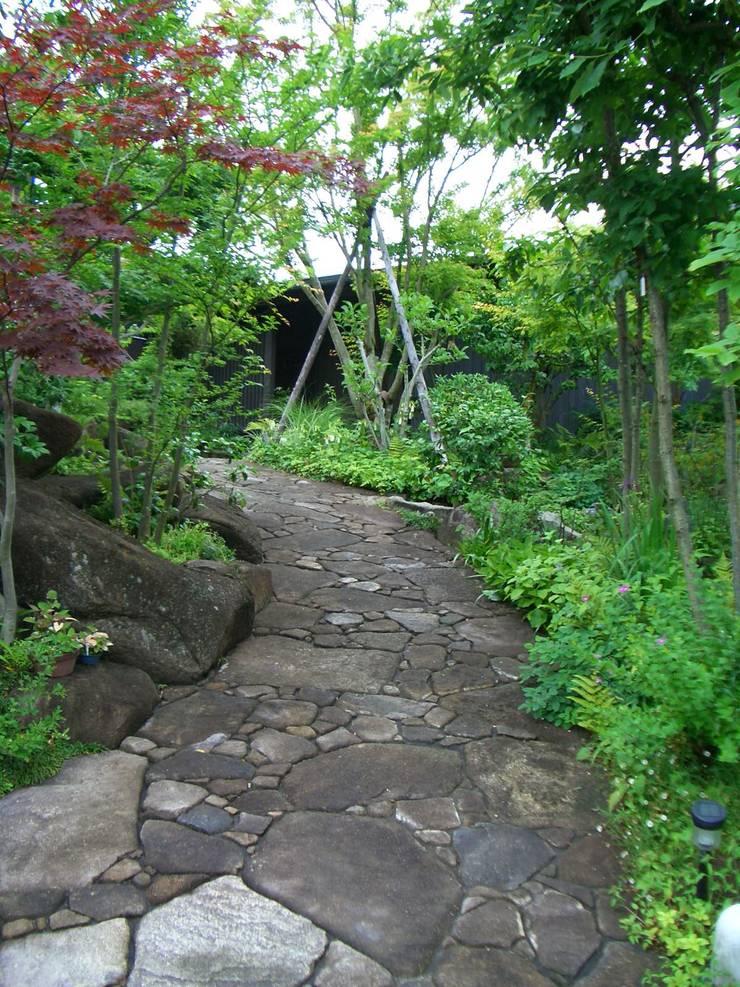 玄関へのアプローチ。: 酒井光憲・環境建築設計工房が手掛けた庭です。,