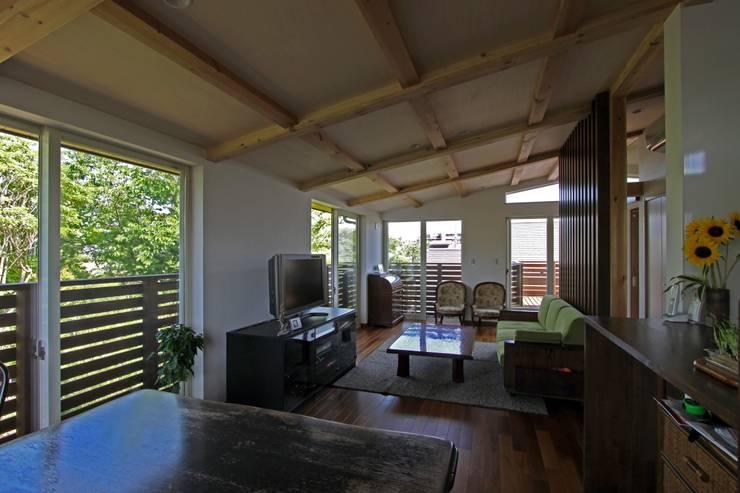 回廊テラスで緑と接する2世帯住宅: アトリエグローカル一級建築士事務所が手掛けたリビングです。