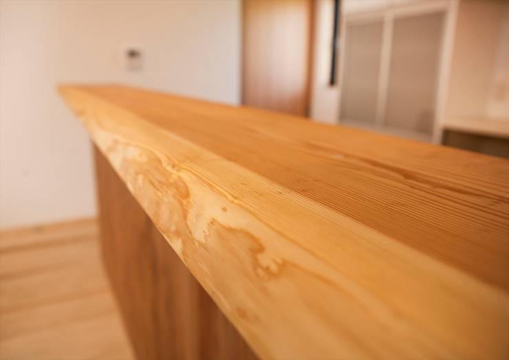 キッチン対面カウンターは、杉の無垢板!: ナイトウタカシ建築設計事務所が手掛けた壁です。,