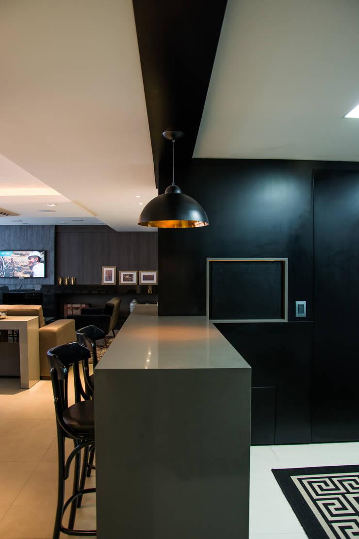 Painel em laca preta escondendo churrasqueira: Salas de estar  por Michele Moncks Arquitetura,Moderno