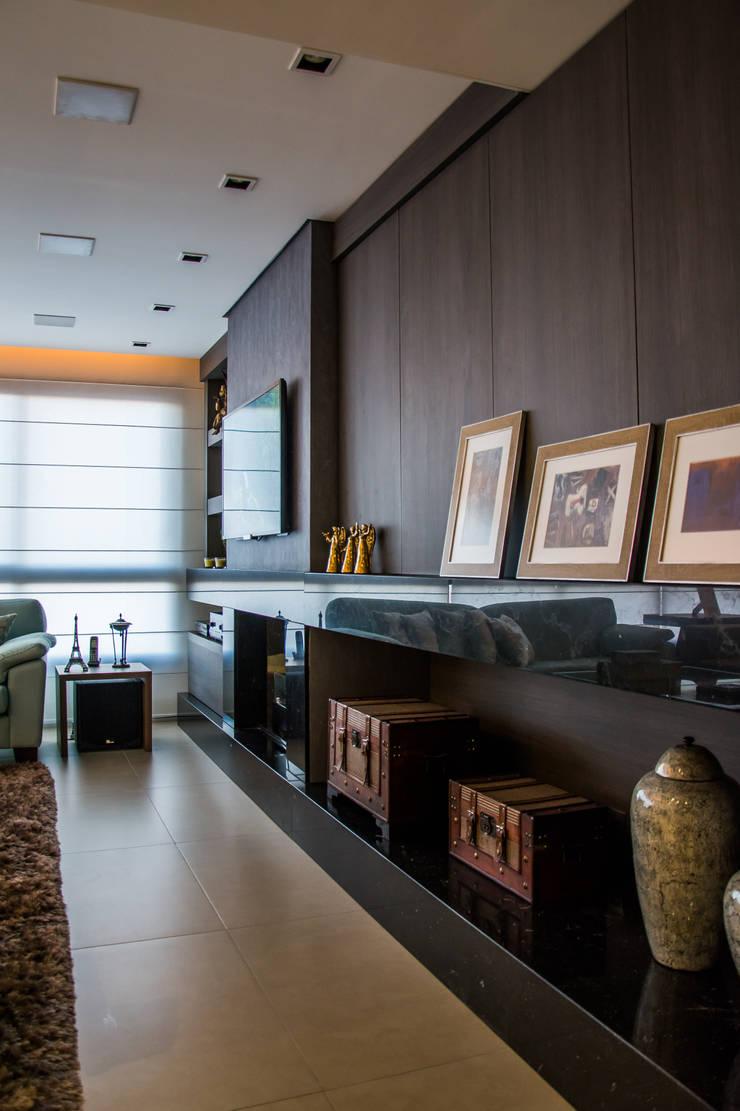 Painel esconde armário com porta sem fecho toque: Salas de estar  por Michele Moncks Arquitetura,Moderno