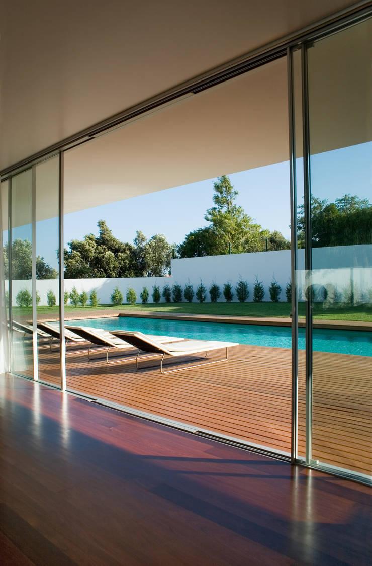 Vista da sala para a piscina: Salas de estar  por A.As, Arquitectos Associados, Lda