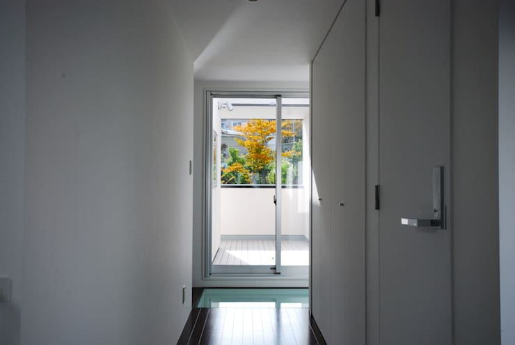 廊下から公園の緑を見る: 株式会社ブレッツァ・アーキテクツが手掛けた廊下 & 玄関です。