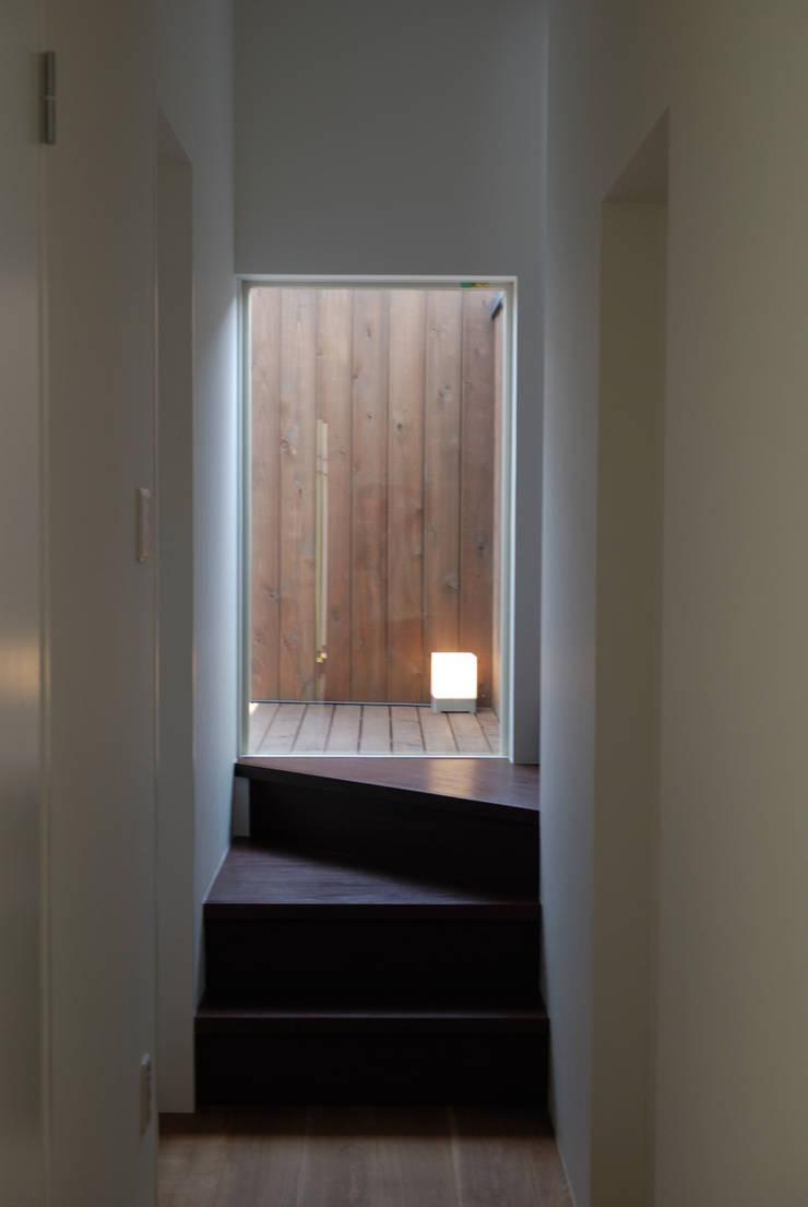 階段からテラスを見る: 株式会社ブレッツァ・アーキテクツが手掛けた廊下 & 玄関です。