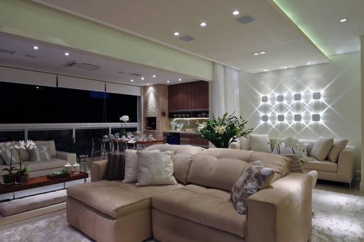 Iluminação de destaque em apartamento no litoral paulista : Salas de estar  por Guido Iluminação e Design