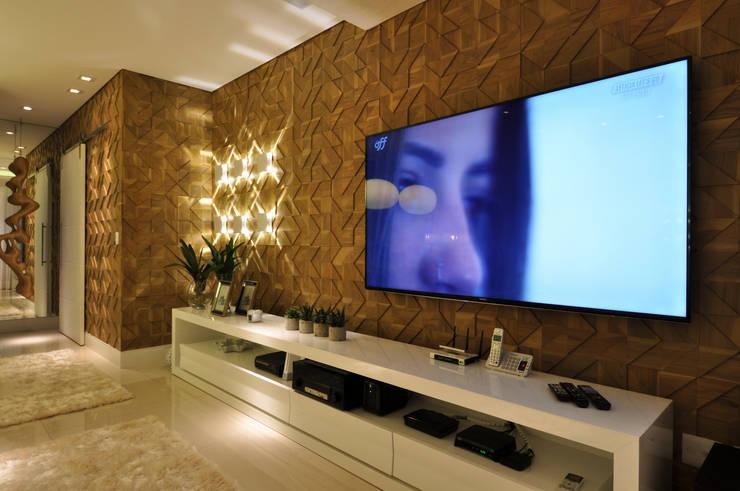 Iluminação de destaque em apartamento no litoral paulista : Salas multimídia  por Guido Iluminação e Design