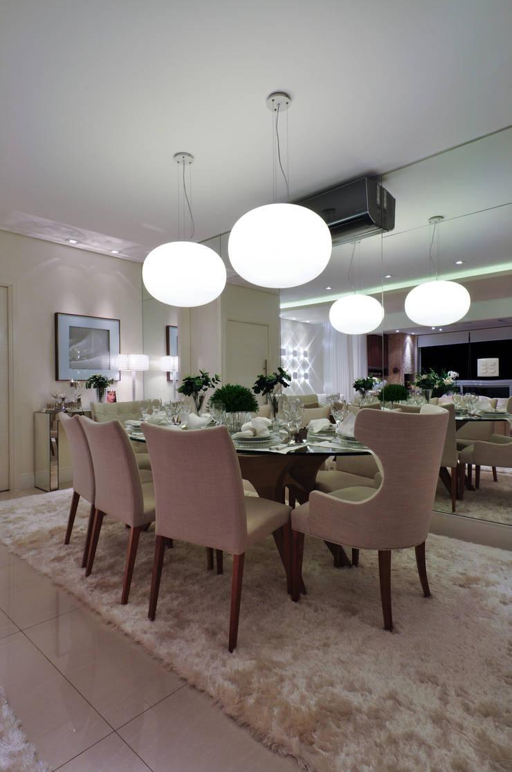 Iluminação de destaque em apartamento no litoral paulista : Salas de jantar  por Guido Iluminação e Design