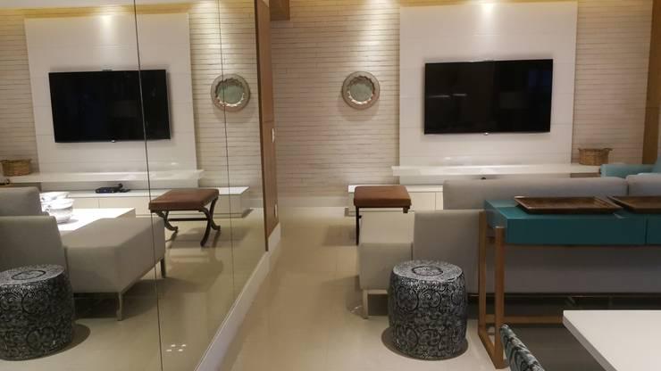 Detalhes living com a utilização de espelhos, marcenaria e revestiventos.: Salas de estar  por Lucio Nocito Arquitetura e Design de Interiores ,