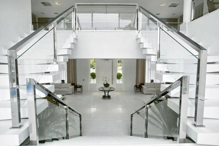 Branco como protagonista nesta casa no litoral brasileiro .: Corredores e halls de entrada  por Bianka Mugnatto Design de Interiores,Eclético Ferro/Aço