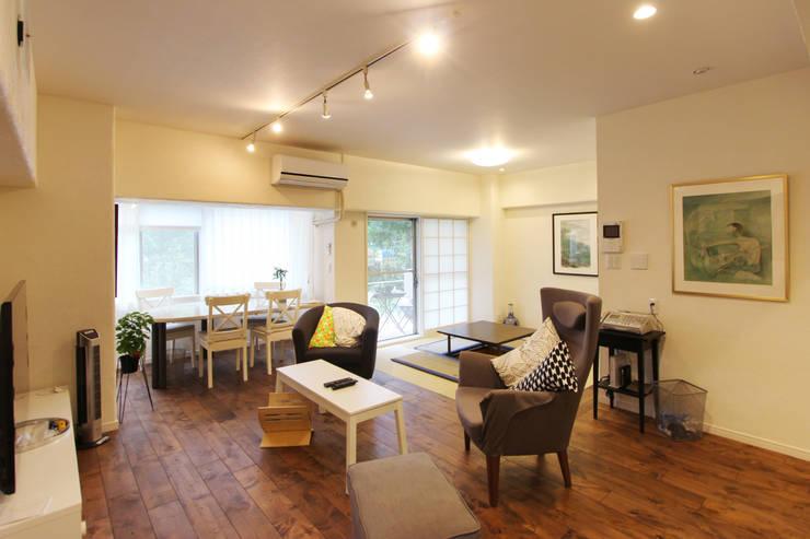 お洒落な大人の空間: 有限会社横田満康建築研究所が手掛けたリビングルームです。,