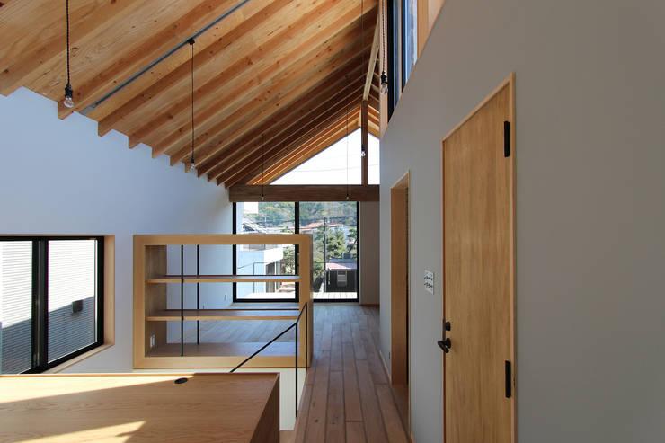 オープンな書斎から階段を経てリビング方向をみた風景: 今津修平/株式会社MuFFが手掛けたリビングです。