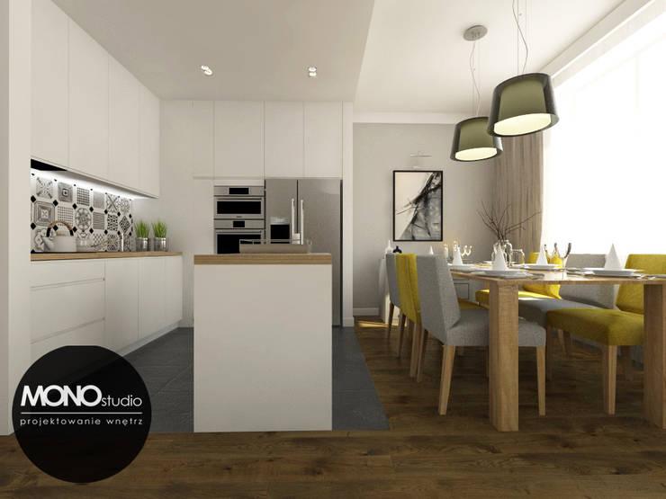 Nowoczesna otwarta na salon kuchnia w minimalistycznym charakterze z dodatkiem ciepłego drewna i koloru: styl , w kategorii Kuchnia zaprojektowany przez MONOstudio