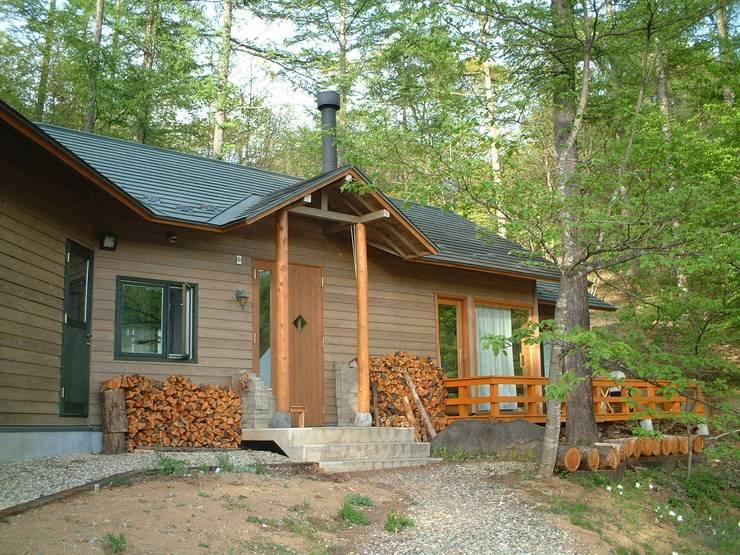 玄関周辺と木製デッキ、カラマツにこだわる: (有)岳建築設計が手掛けた家です。