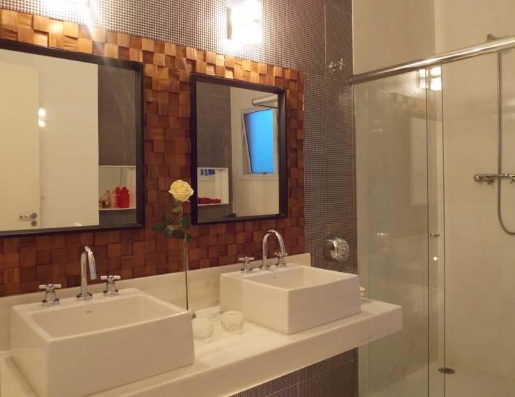 Banho suíte - Painel de teca e espelhos: Banheiros  por Lúcia Vale Interiores,