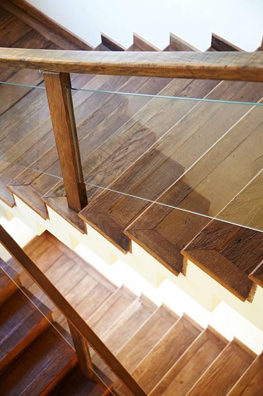 Escada revestida em madeira de demolição e guarda-corpo em vidro: Corredores e halls de entrada  por Moran e Anders Arquitetura