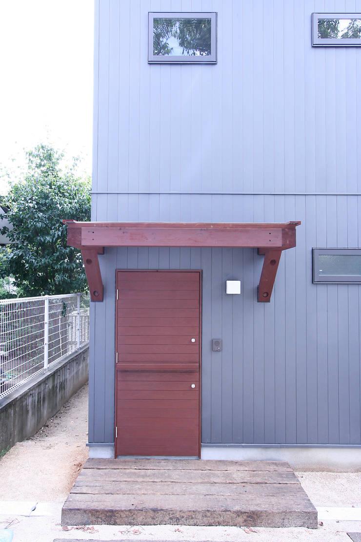 庇+玄関ドア: 士が手掛けた窓です。,モダン 木 木目調