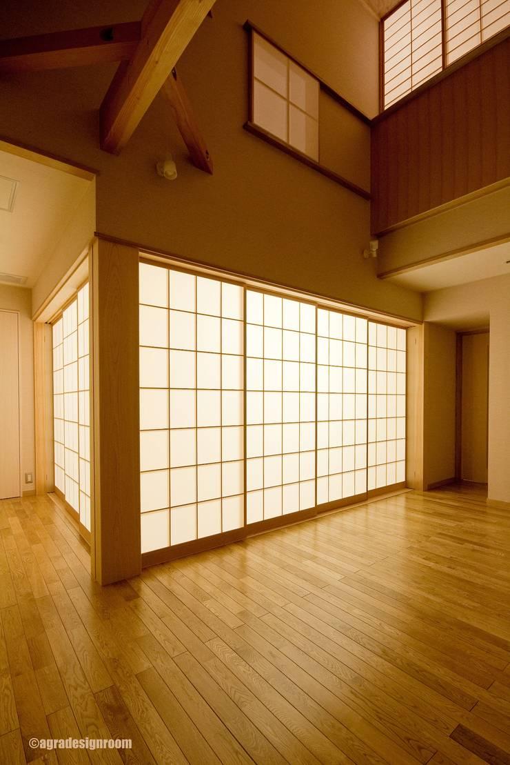 そして和室は、大きな行燈に変わる  Y la habitación de estilo japonés se convierte en una gran linterna.: アグラ設計室一級建築士事務所 agra design roomが手掛けたリビングルームです。