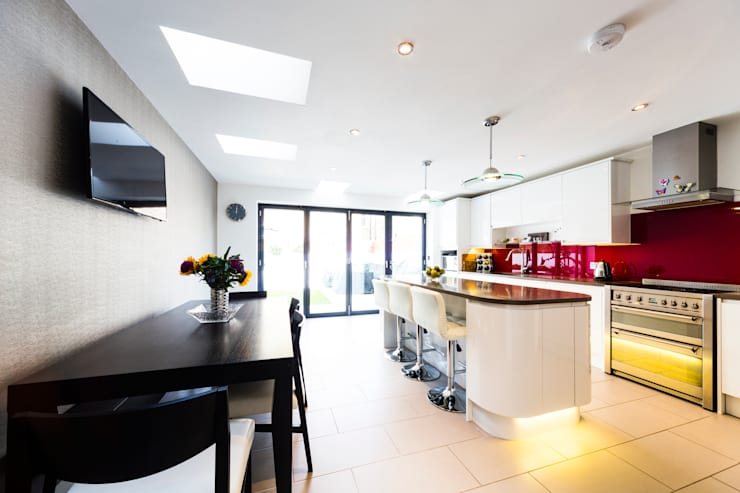 White kitchen with red splashback, modern kitchen pendants, bifold doors, black dining table and chairs:  Kitchen by Affleck Property Services