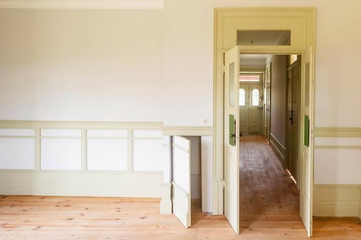 Vista interior - sala e corredor: Salas de estar  por Clínica de Arquitectura