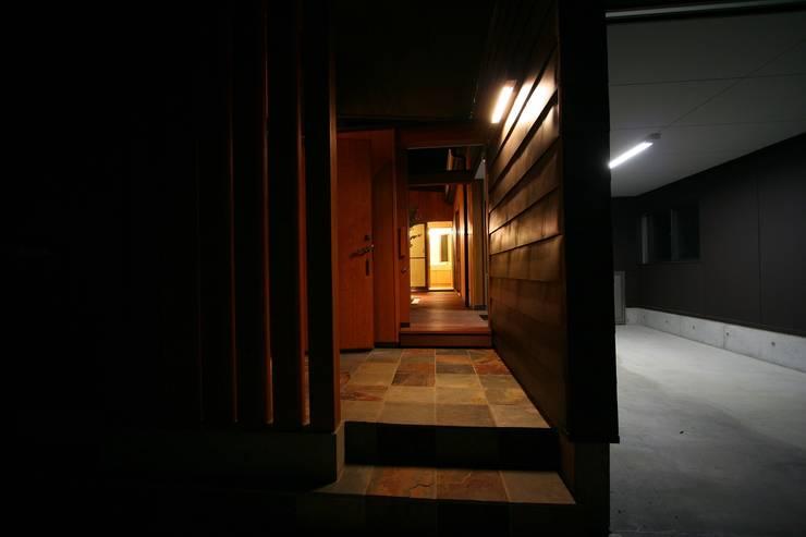 アプローチから中庭を見る: 遠藤知世吉・建築設計工房が手掛けた廊下 & 玄関です。,