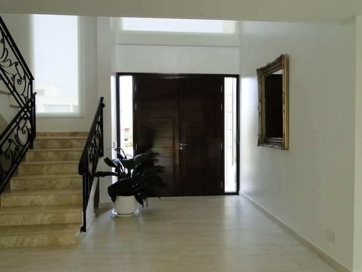 Casa en Castores – Nordelta: Pasillos y recibidores de estilo  por Arquitectos Building M&CC - (Marcelo Rueda, Claudio Castiglia y Claudia Rueda)