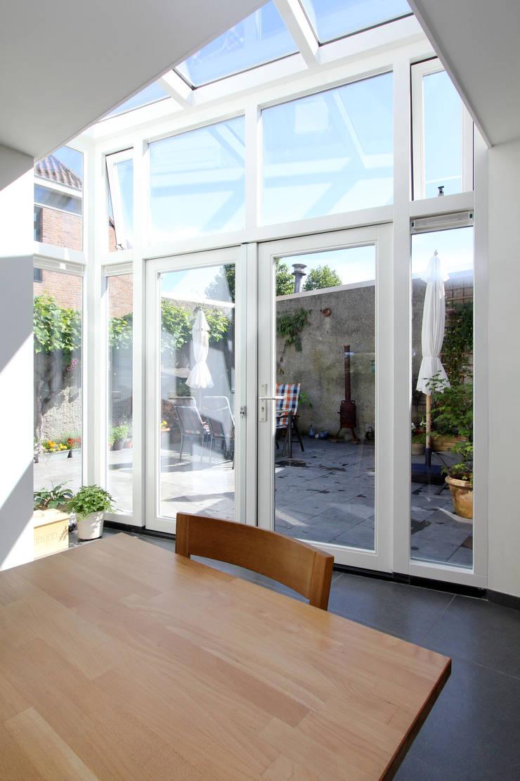 doorkijk vanuit woon- eetkamer naar binnenplaats:  Eetkamer door JANICKI ARCHITECT, Modern
