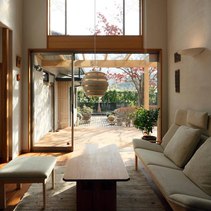 居間からテラス: 竹内建築設計事務所が手掛けたリビングです。