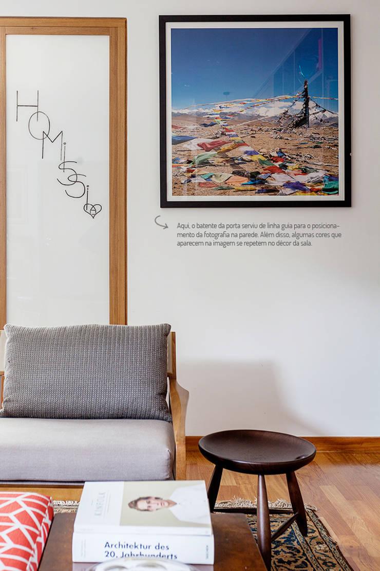 Paredes decoradas com fotografias.: Sala de estar  por Casa de Valentina,