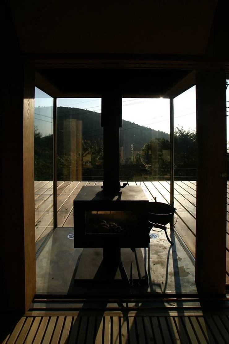 薪ストーブ: 樋口善信建築計画事務所が手掛けたテラス・ベランダです。