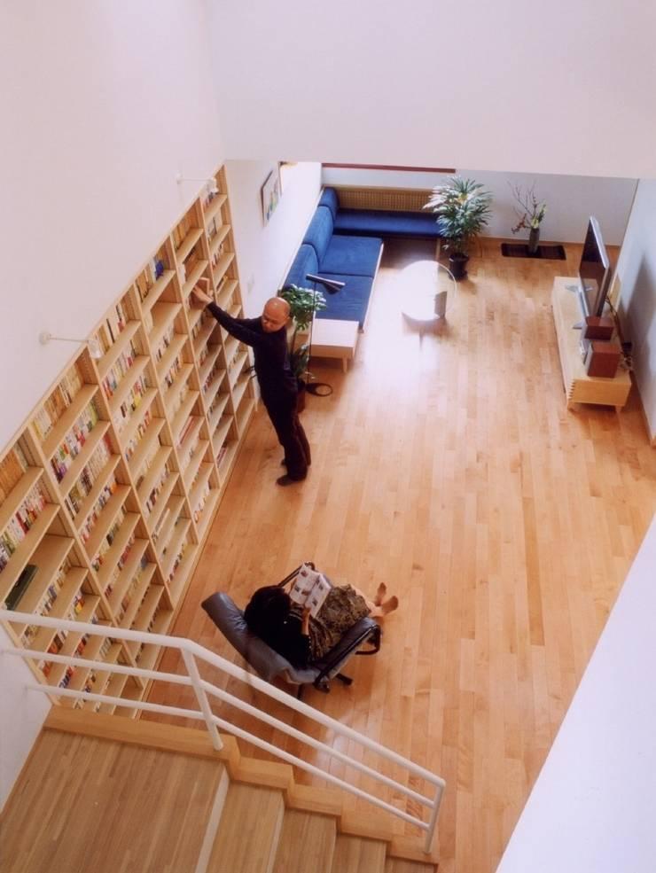 本棚に囲まれた一室空間の家: 一級建築士事務所 株式会社 空間スタジオが手掛けたリビングです。