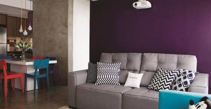 Cimento e muita cor no apartamento personalizado: Salas de estar  por Lima Orsolini Arquitetura e Interiores