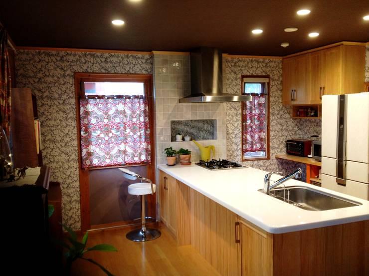 赤を基調にしたカーテンで元気な空間を演出する: HONEY HOUSEが手掛けたキッチンです。