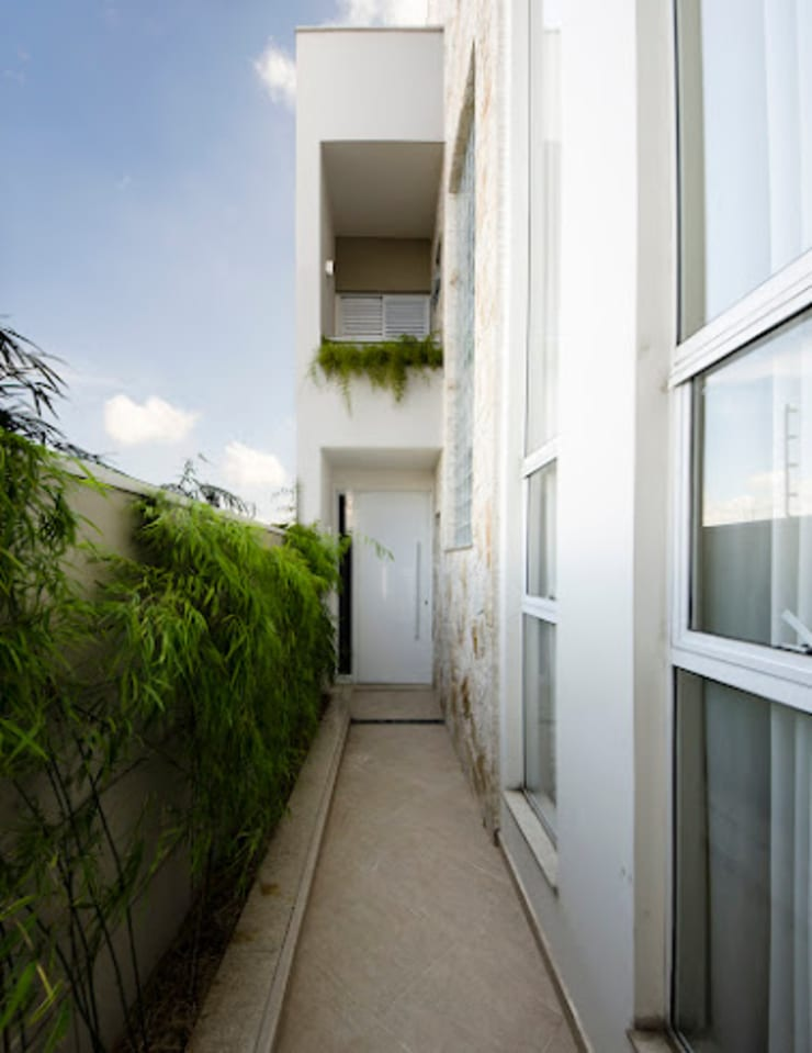 Lote estreito casa espaçosa.: Corredores e halls de entrada  por Magno Moreira Arquitetura