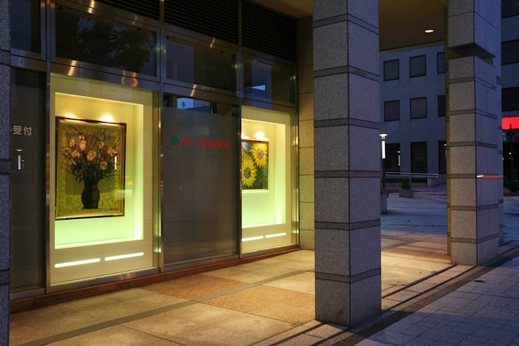 薬局 外観部分(通りに向けた画廊風ディスプレイ 絵画 夕方): 吉田設計+アトリエアジュールが手掛けた医療機関です。