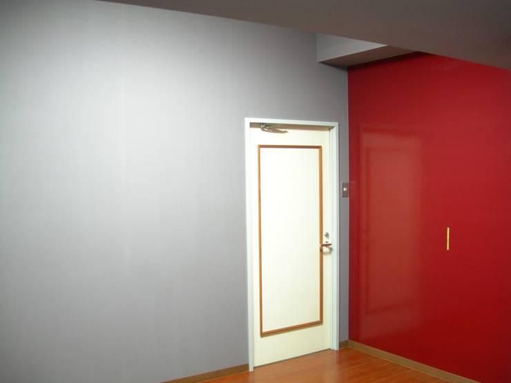 寝室に赤のアクセントポイントクロスですが何か?: インテリア研究事務所が手掛けた寝室です。,
