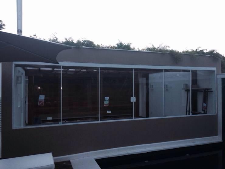 Vista da garagem pela piscina.: Garagens e edículas  por Studio HG Arquitetura,