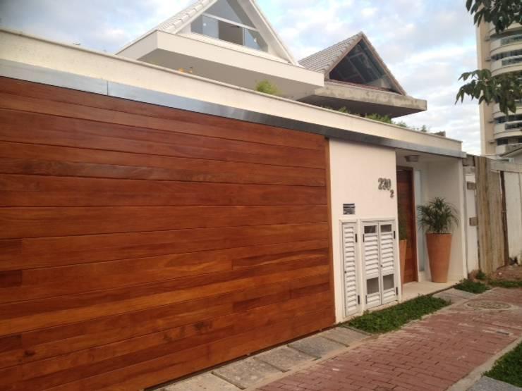 Portão da garagem deslizante em madeira.: Garagens e edículas  por Studio HG Arquitetura,