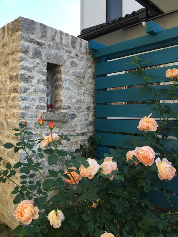 石積の壁とウッドフェンスを: eniが手掛けた庭です。