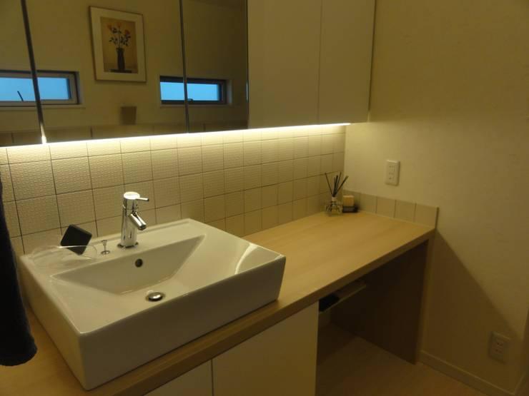 洗面化粧台: DIOMANO設計が手掛けたウォークインクローゼットです。,