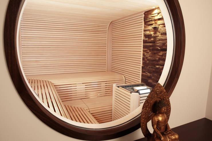 Blick in die Sauna durch rundes Fenster:  Spa von Erdmann Exklusive Saunen