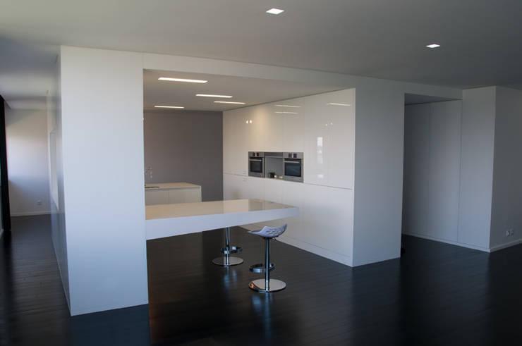 cozinha vista da sala de estar: Cozinhas  por feedback-studio arquitectos