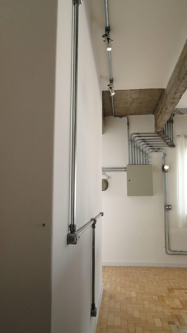 tubulação aparente: Corredores e halls de entrada  por omnibus arquitetura,