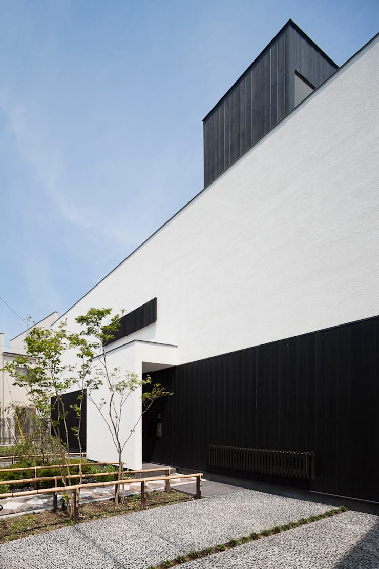 白壁と板壁で構成された外観: 根來宏典建築研究所が手掛けた家です。,