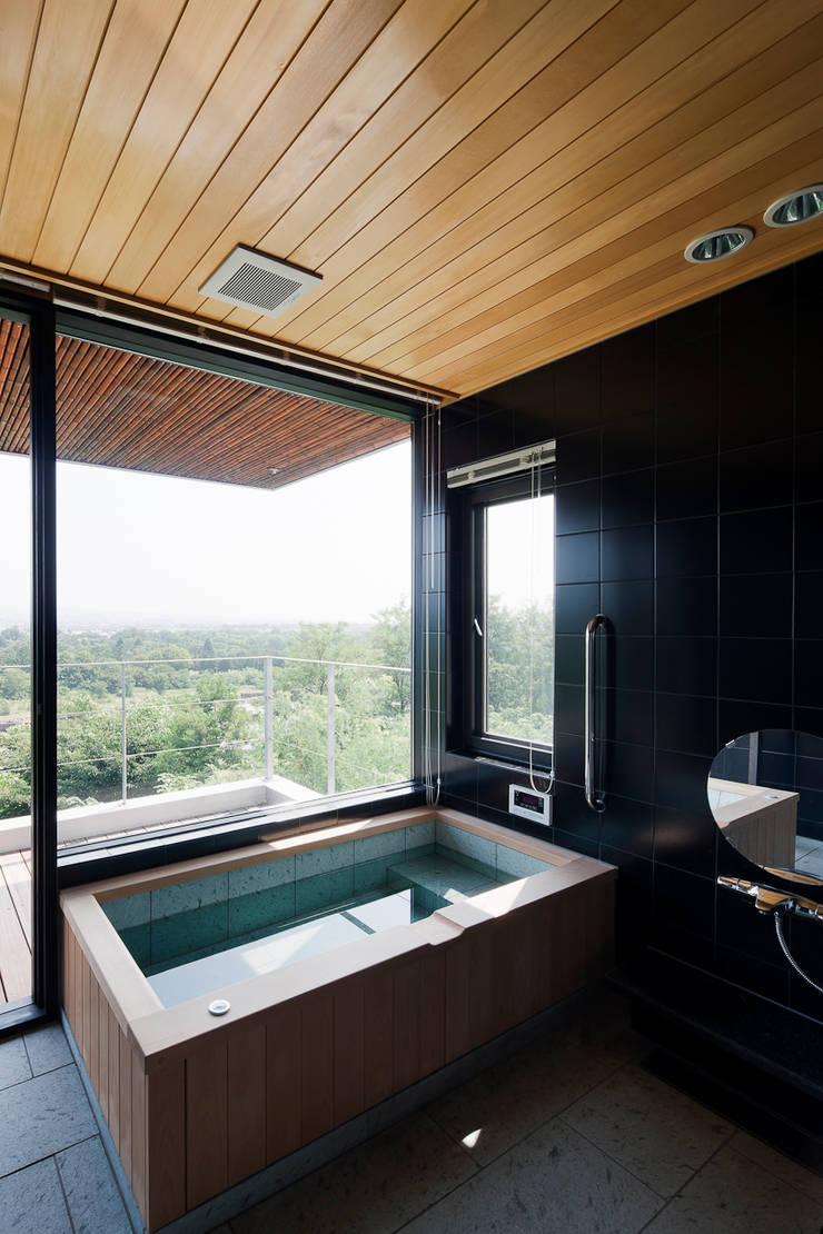 自然の風合いを活かした浴室: 根來宏典建築研究所が手掛けた浴室です。,