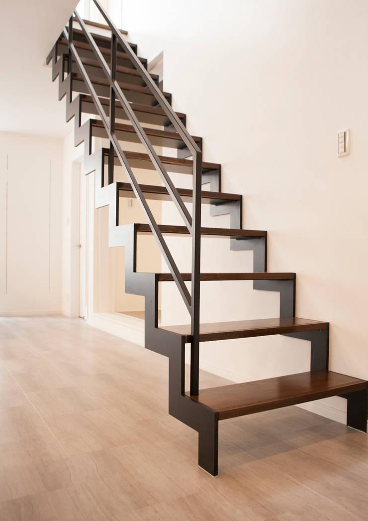 開放感のある、オブジェのようなイナズマ階段: ナイトウタカシ建築設計事務所が手掛けた廊下 & 玄関です。