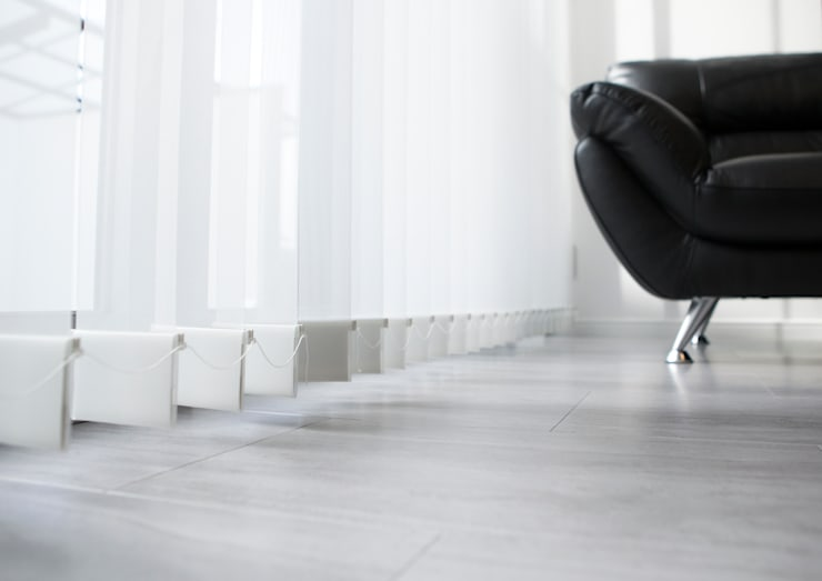 石目の床と縦型ブラインドの組み合わせ: ナイトウタカシ建築設計事務所が手掛けた壁です。